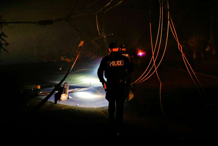 Police officers investigate downed wires on Pearson Road after the Camp Fire ravaged the town of Paradise, California, on Friday, Nov. 9, 2018.