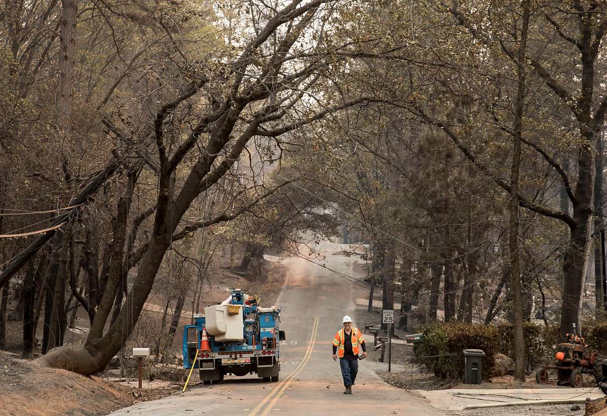 A PG&E employee walks down Edgewood Lane Sunday, Nov. 11, 2018 after the Camp Fire ripped through the town of Paradise, Calif.