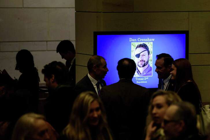 A TV shows the image of incoming U.S. Rep. Dan Crenshaw during a slideshow of new members as people arrive for a House of Representatives member-elect welcome briefing on Capitol Hill in Washington, D.C.
