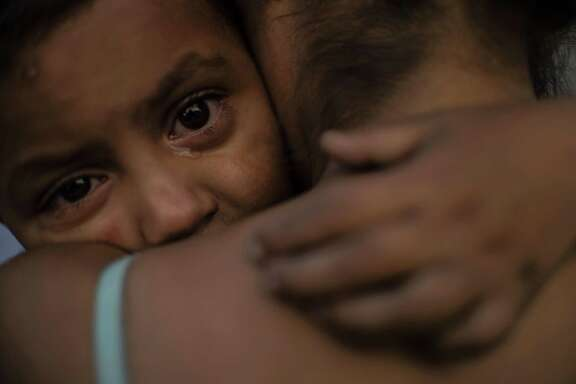 A Central American migrant child moving with a caravan towards the United States in hopes of a better life, cries as she embraces a woman at the Alfa y Omega shelter in Mexicali, Baja California state, Mexico, on November 16, 2018. - The Central American migrant caravan trekking toward the United States converged on the US-Mexican border Thursday after more than a month on the road, undeterred by President Donald Trump's deployment of thousands of American troops near the border. (Photo by PEDRO PARDO / AFP)PEDRO PARDO/AFP/Getty Images