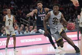 Iowa forward Tyler Cook (25) drives to the basket past UConn forward Tyler Polley (12) during the the 2K Empire Classic championship on Friday at Madison Square Garden in New York.