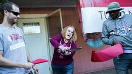Suzan Trout cut the inauguration ribbon to her renovated house during the Welcome Home party for the Trout family hosted by the Team Rubicon, a veteran-led global disaster response organization, Friday, Nov. 16, 2018, in Houston. To her right holding the ribbon is John Bickham, the Team Rubicon carpenter of the project and to her left is Jason Asnes, the  Team Rubicon site supervisor.
