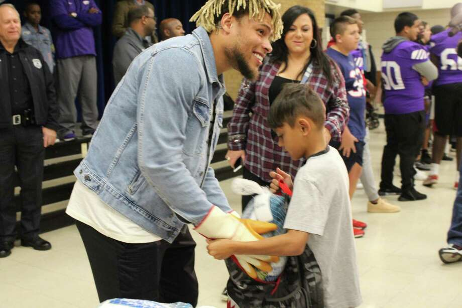 Houston Texan Tyrann Mathieu puts a turkey in a child's backpack. Photo: Kaila Contreras