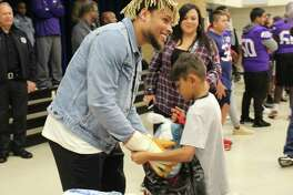 Houston Texan Tyrann Mathieu puts a turkey in a child's backpack.