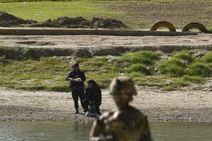 Mexican nationals fish on the Nuevo Laredo, Mexico, side of the Rio Grande while the U.S. military installs concertina wire along the river's banks on Friday, Nov. 16, 2018 as they reinforce the border and ports of entry in Laredo, Texas.