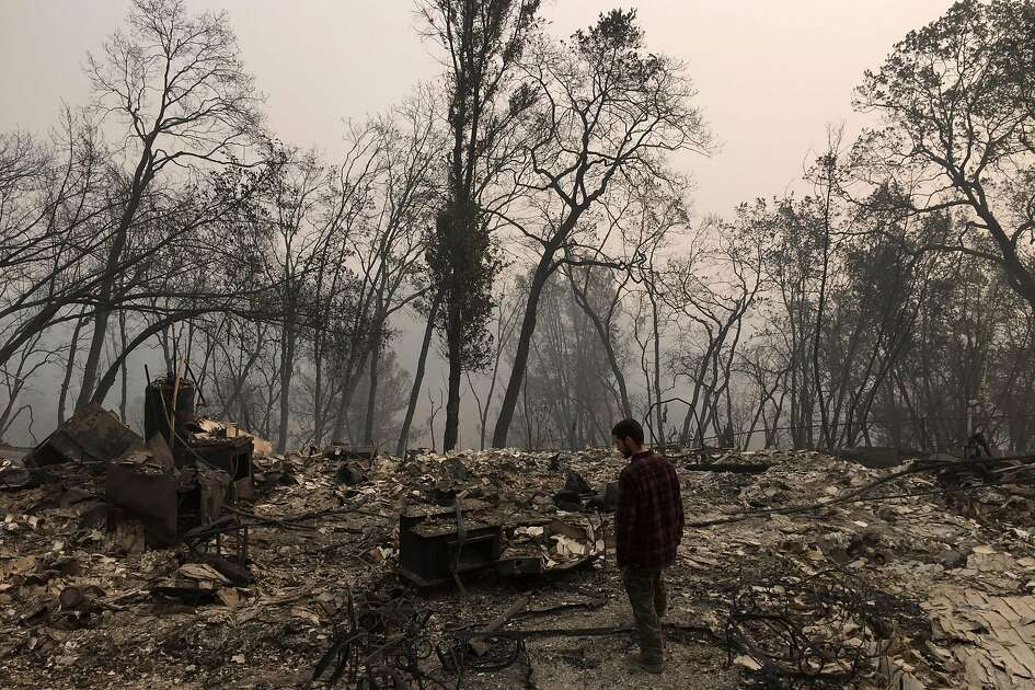 TOPSHOT - Jhonathan Clark walks in what was his house, destroyed by Camp fire, in Paradise, California, on November 15, 2018. - Jhonathan Clark was speechless, with his hands on his head he began to walk through the sea of rubble in which his house in Paradise became, a village massacred by fire. His great concern now is to find his brother Maurice, his sister in law and his six year old nephew, of whom he has had no news since hell began. Fire Camp claimed the lives of at least 63 people and 631 are reported missing, authorities said on November 15, 2018. (Photo by Javier TOVAR / AFP)JAVIER TOVAR/AFP/Getty Images