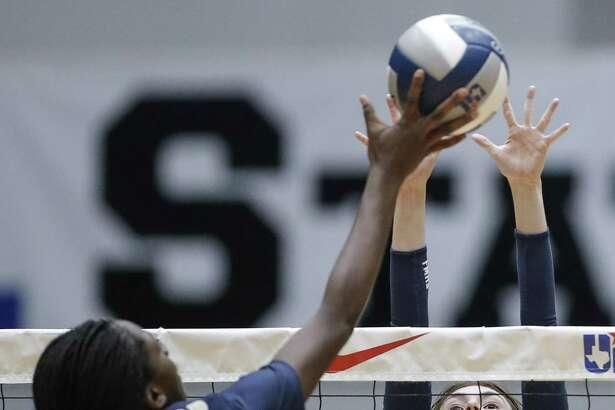 O'Connor senior Emmy Ogogor (17) spikes the ball as Flower Mound sophomore Hailey Hutchings (5) blocks.