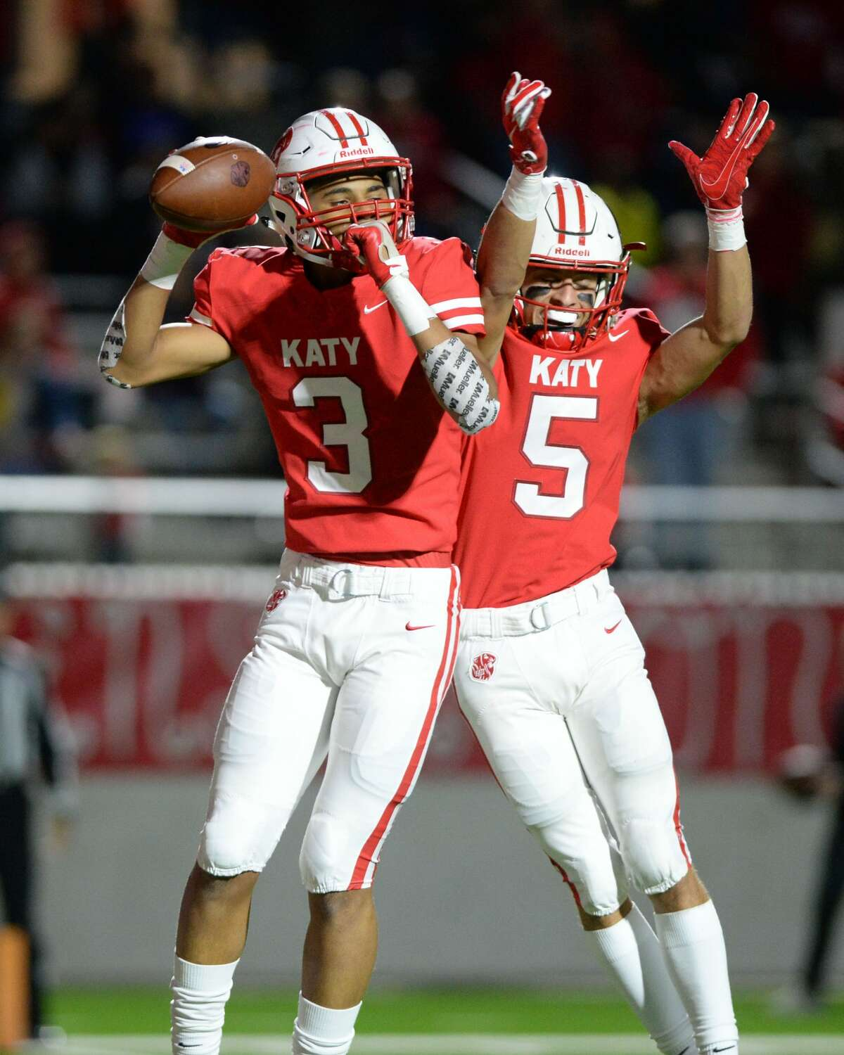 CJ Baskerville (3) and Steven Stiles (5) of Katy celebrate a touchdown in the second quarter of a Class 6A Div. I Reg. III bi-district playoff game between the Katy Tigers and the Travis Tigers on Friday, November 16, 2018 at Legacy Stadium, Katy, TX.