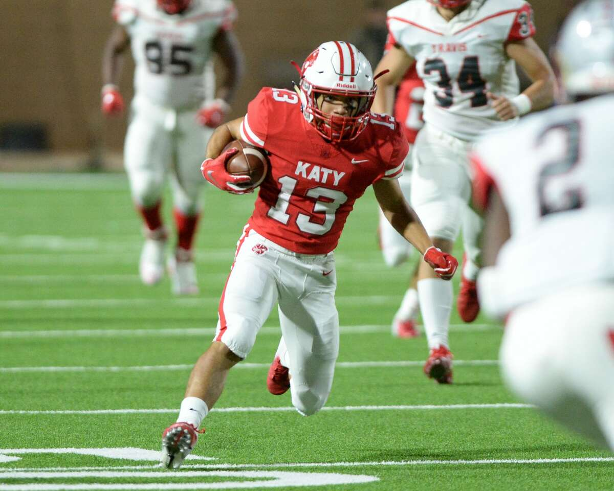Jordan Patrick (13) of Katy carries the ball in the first quarter of a Class 6A Div. I Reg. III bi-district playoff game between the Katy Tigers and the Travis Tigers on Friday, November 16, 2018 at Legacy Stadium, Katy, TX.