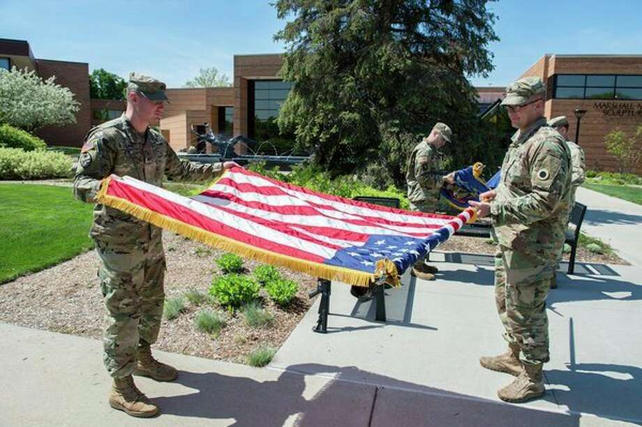 Military service members unfurl the American flag for use during Saginaw Valley State University's Memorial Day commemoration event for the campus community and the general public on May 23. (Photo provided/Michael Randolph, SVSU)