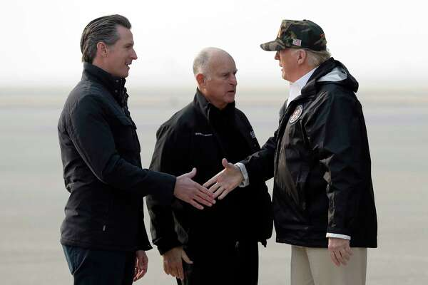 President Donald Trump greets California Gov.-elect Gavin Newsom as he arrives on Air Force One at Beale Air Force Base for a visit to areas impacted by the wildfires, Saturday, Nov. 17, 2018, at Beale Air Force Base, Calif., as Gov. Jerry Brown, stands at center.