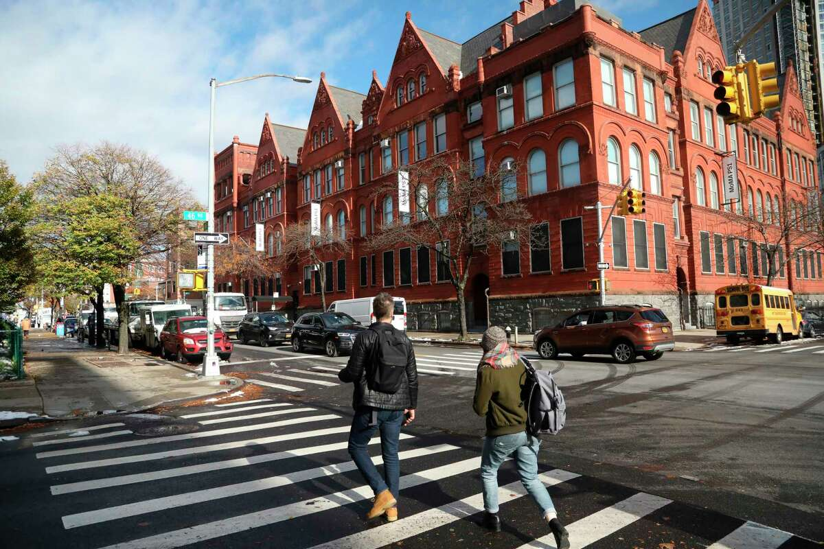 People cross the street next to the MOMA PS1 art museum located in Long Island City near the site for a proposed Amazon headquarters in the Queens borough of New York, Friday, Nov. 16, 2018. While some residents are optimistic about Amazon moving into their neighborhood, others have doubts about whether they will be able to get any of the thousands of jobs the company is promising to bring to the area.