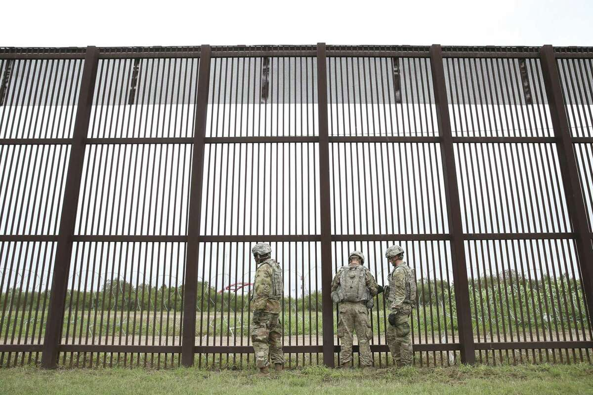 Soldiers secure razor wire to the U.S./Mexico border wall near downtown Brownsville, Texas, Monday, November 12, 2018. Around 5,800 troops were deployed for the border mission. U.S. President Donald Trump ordered the deployment in response to a migrant caravan from Central America.