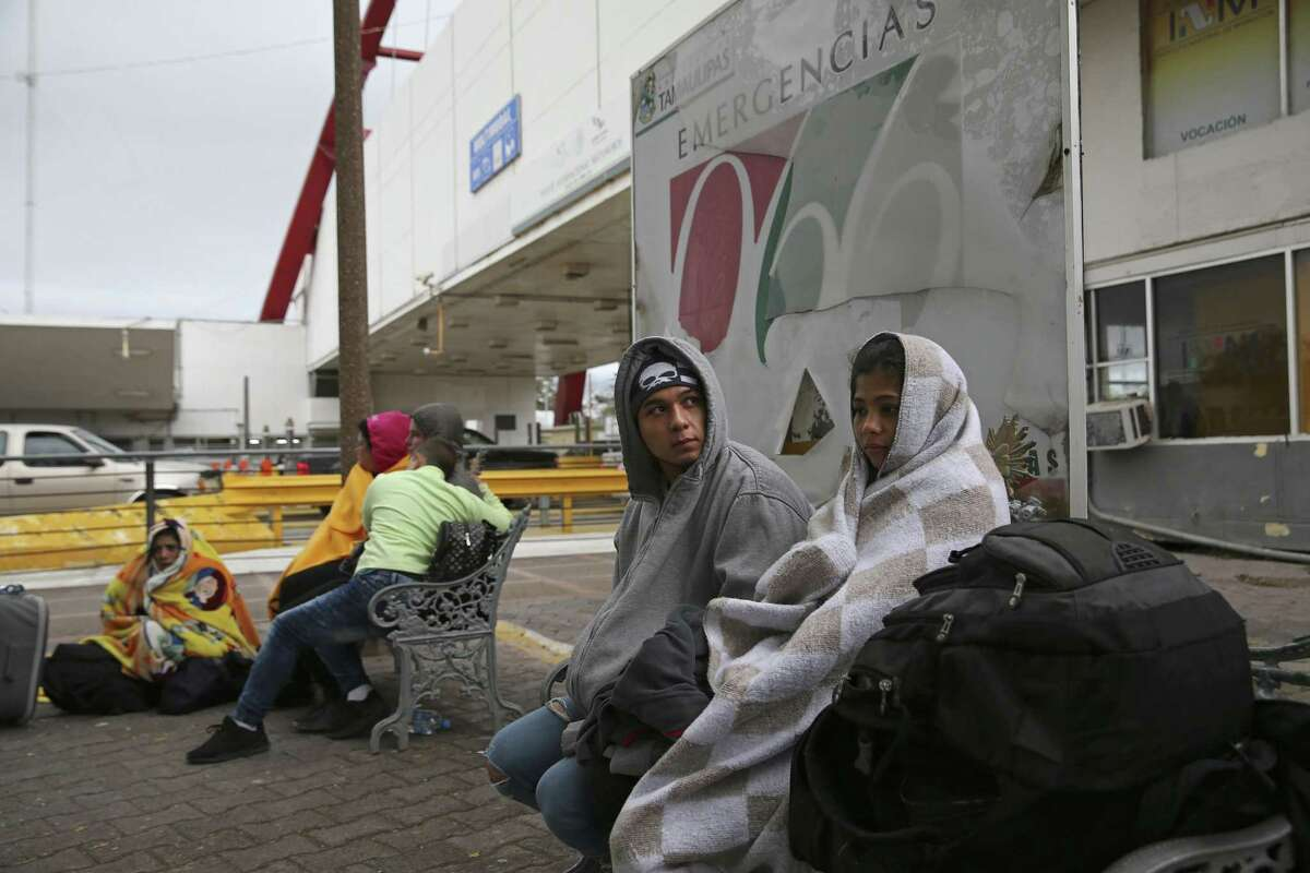 Johnson Hernandez Maldonado, 19, and his girlfriend, Maryuri Yadira Contreras Hernandez, 20, wait by the Mexican immigration offices at the Matamoros-Brownsville International Bridge, Monday, November 12, 2018. The couple, from Honduras, was waiting to seek asylum in the U.S. Immigrants from Cuba and other countries were also in the group waiting by the bridge.