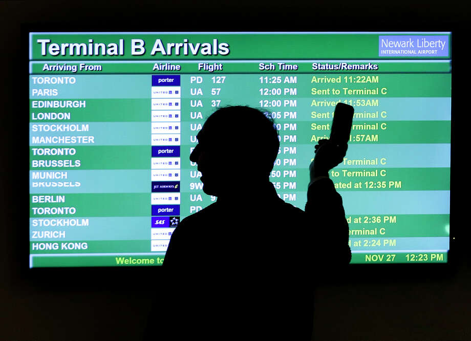 FILE - In this Nov. 27, 2013, file photo, a person points to a screen with an airplane travel list while holding up a phone at Newark Liberty International Airport in Newark, N.J. International air travel has become remarkably safe in recent years, with deadly accidents like last month's Lion Air crash in Indonesia becoming more rare. (AP Photo/Julio Cortez, File) Photo: Julio Cortez / AP2013