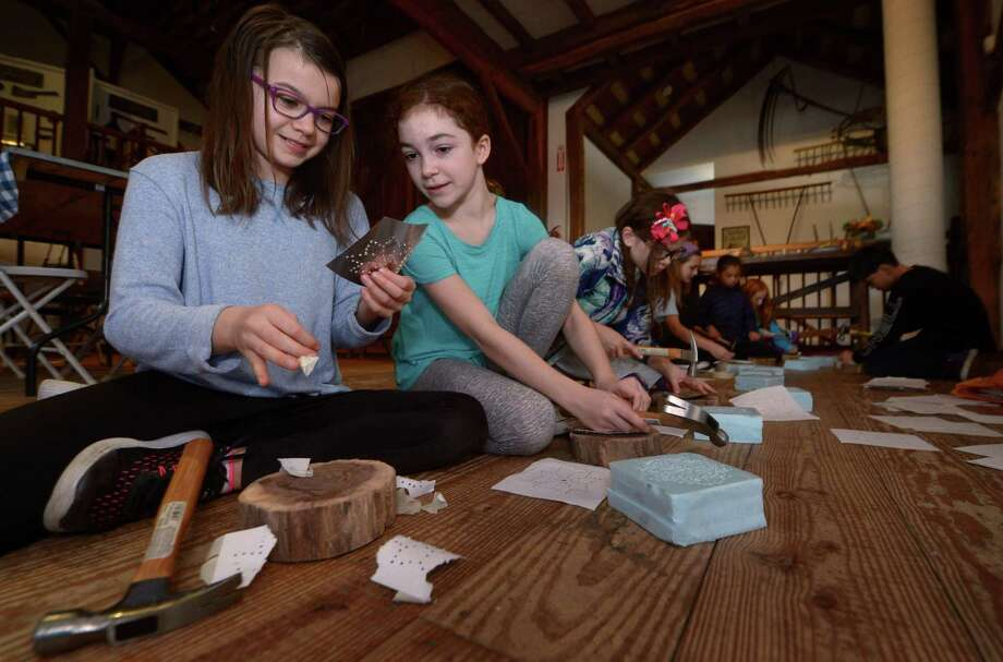 "Wilton residents Lena O'Malley, 11, and Sarah Manners, 11, make punch ""tin"" candle holders during the Wilton Historical Society Tinsmithing Workshop Saturday, November 17, 2018, at the Historical Society in Wilton, Conn. During the workshop the Museum Educator talked about the history of tinsmiths and the important items they produced, including cookie cutters. Photo: Erik Trautmann / Hearst Connecticut Media / Norwalk Hour"
