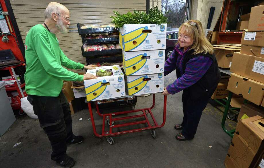 Trader Joe's employee J.D. Smith helps Food Rescue US volunteer Lyn DeTroy as she picks up food from Trader Joe's in Westport Thursday, November 15, 2018, for delivery to the Family and Children's Agency in Norwalk, Conn. Food Rescue US, transfers usable food from grocers, restaurants, catering events, to food insecure families throughout the U.S. Photo: Erik Trautmann / Hearst Connecticut Media / Norwalk Hour