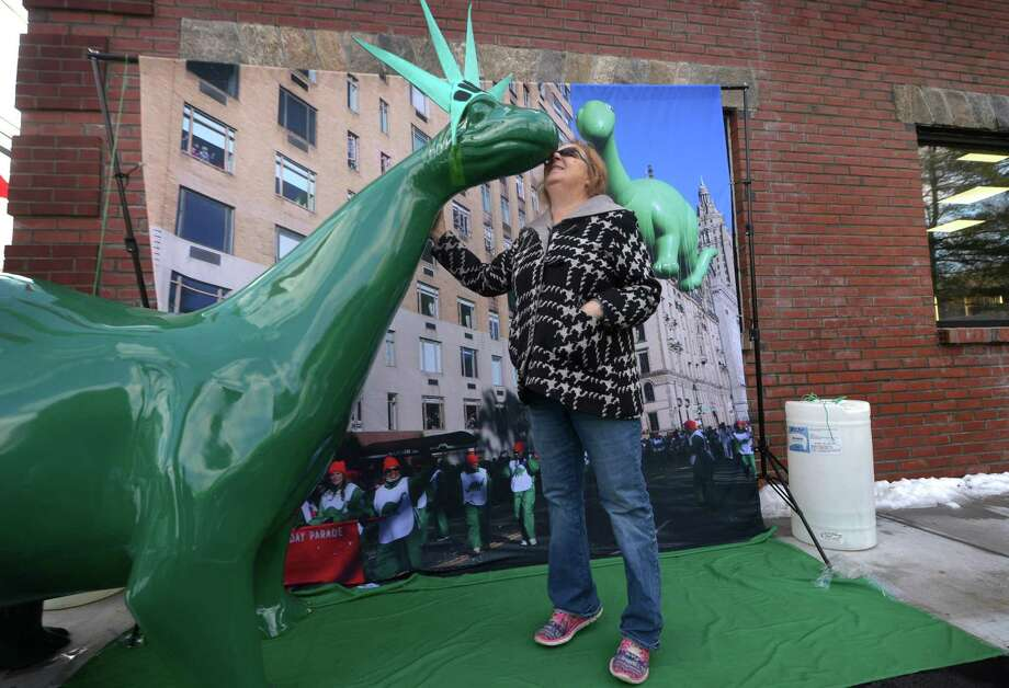 Donna Delorenzo of North Haven drove an hour to have her photo taken with DINO as the Sinclair green dinosaur makes one of several stops Saturday, November 17, 2018, in his annual trek across America at the Main Ave. Sinclair gas station in Norwalk, Conn. The tour will culminate in New York City where an inflatable version of DINO will makes his fourth annual appearance in The 92nd Macys Thanksgiving Day Parade taking place on Thursday, November 22nd. Photo: Erik Trautmann / Hearst Connecticut Media / Norwalk Hour