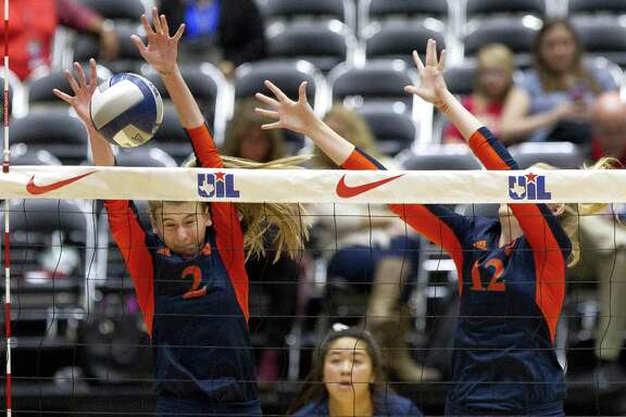 Katy Seven Lakes setter Morgan Janda (2) blocks a shot from Lewisville Hebron setter Nicole Drewnick (5) beside middle blocker Cassidy Nimtz (12) during the first set of the Class 6A state championship at the Curtis Culwell Center, Saturday, Nov. 18, 2017, in Garland.