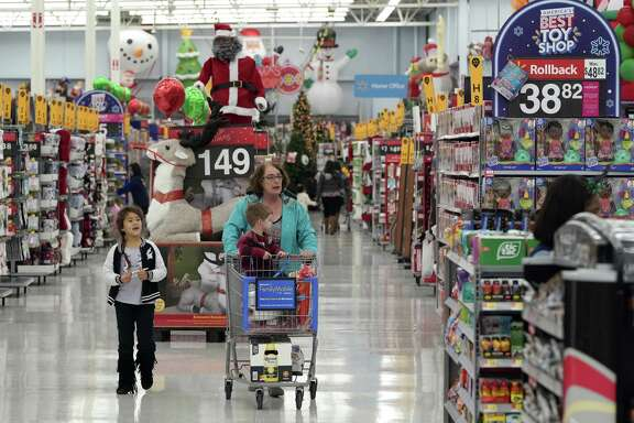 In this Friday, Nov. 9, file photo shoppers walks down an isle at a Walmart Supercenter in Houston. On Wednesday, Nov. 14, the Labor Department reports on U.S. consumer prices for October.