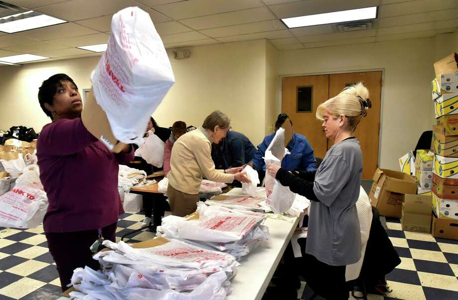 New Haven,  Connecticut, November 17, 2018:  Christian Community Action board member Lynette E. Johnson of New Haven, left, and Andrea Sly of Simsbury, a blumshapiro employee, right,  prepare shopping bags for packing food Saturday as  more than 30 blumshapiro employees and their families, community volunteers and Christian Community Action employees help Christian Community Action of New Haven prepare hundreds of bags of Thanksgiving Day meals  during the  seventh annual blumshapiro Thanksgiving Food Basket Campaign for Christian Community Action at Casa de Adoracion y Oracion on Columbus Avenue in New Haven. The annual volunteer food campaign will feed more than 1,200 New Haven families and 3,000 residents. Photo: Peter Hvizdak, Hearst Connecticut Media / New Haven Register