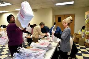 New Haven, Connecticut, November 17, 2018: Christian Community Action board member Lynette E. Johnson of New Haven, left, and Andrea Sly of Simsbury, a blumshapiro employee, right, prepare shopping bags for packing food Saturday as more than 30 blumshapiro employees and their families, community volunteers and Christian Community Action employees help Christian Community Action of New Haven prepare hundreds of bags of Thanksgiving Day meals during the seventh annual blumshapiro Thanksgiving Food Basket Campaign for Christian Community Action at Casa de Adoracion y Oracion on Columbus Avenue in New Haven. The annual volunteer food campaign will feed more than 1,200 New Haven families and 3,000 residents.