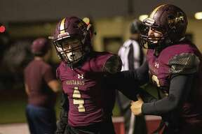 Magnolia West offensive lineman Christian Copher (78) runs to celebrate with Magnolia West wide receiver Payton Finch (4) after Finch scored a touchdown during a Region III-5A (Div. I) bi-district playoff game at Mustang Stadium in Magnolia.