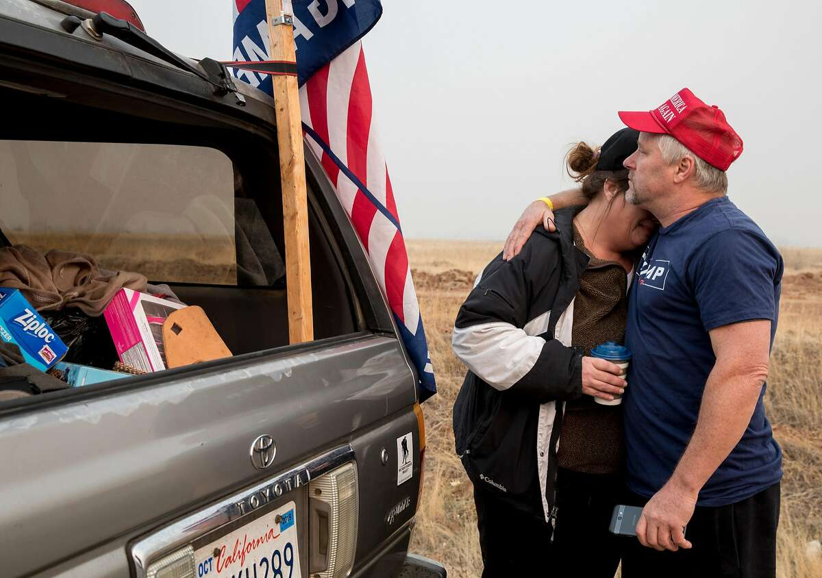 Paradise resident Fred Bowerman comforts his fianc�, Tami Wright, who lost their home in the Camp Fire, as emotions take over while waiting on the side of SkyWay in Chico, Calif. to get a glimpse of President Donald Trump as his motorcade drives into Paradise, Calif. Saturday, Nov. 17, 2018.