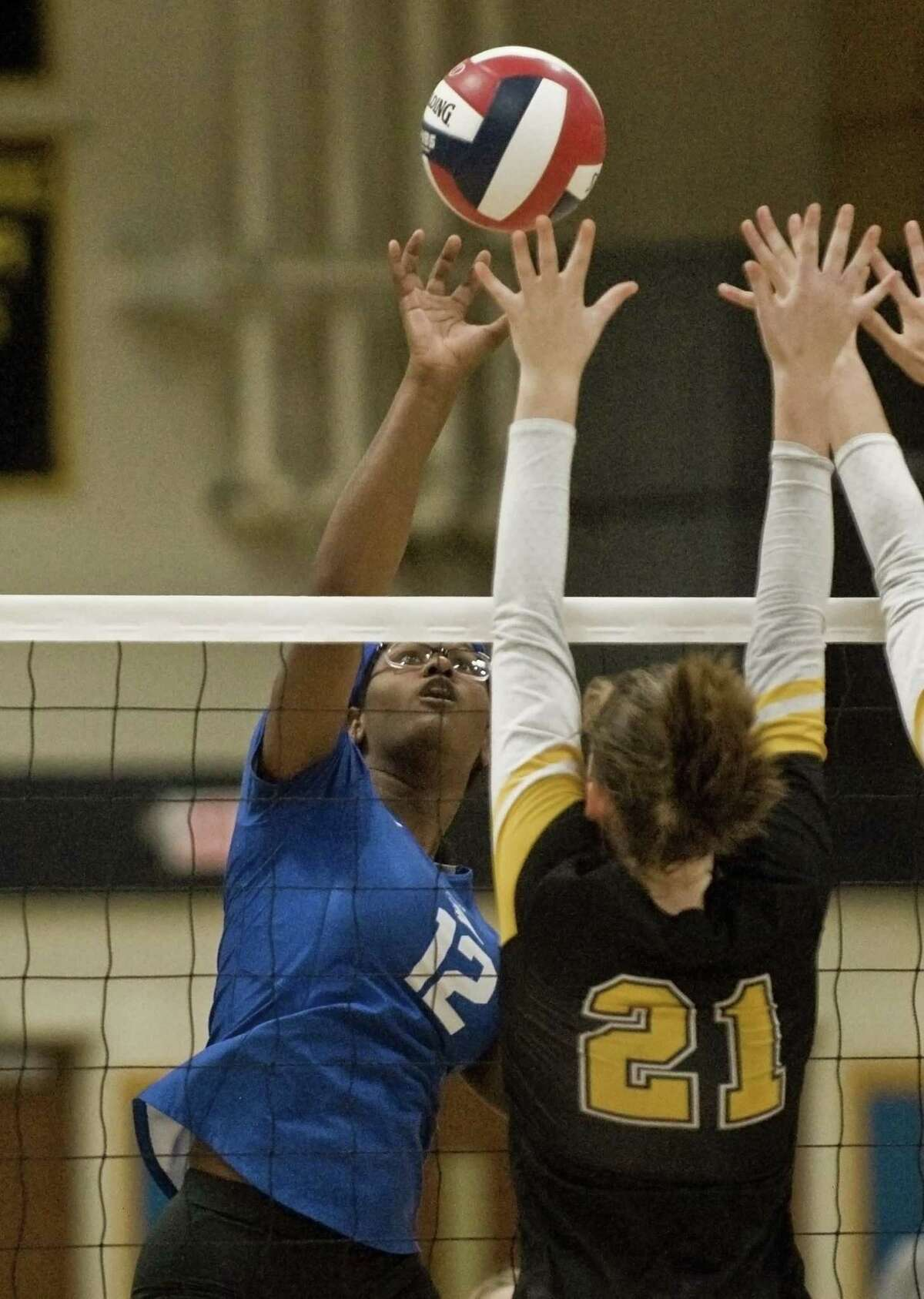 Darien High School's Hassana Arbubakrr tips the ball over the net in the Class LL volleyball championship game against Amity Regional High School, played at East Haven High School. Saturday, Nov. 17, 2018