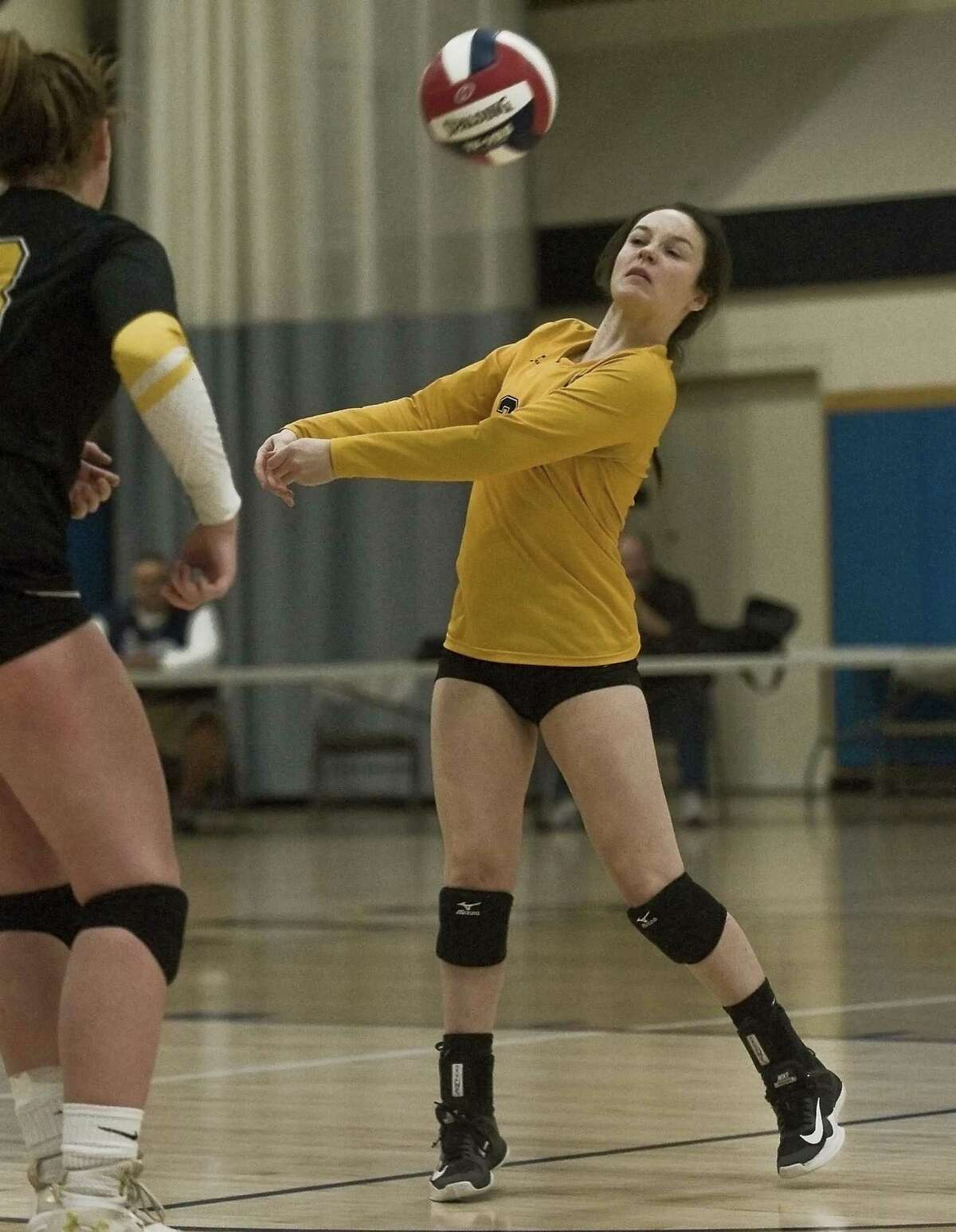 Amity Regional High School's Olivia Pisano returns a serve in the Class LL volleyball championship game against Darien High School, played at East Haven High School. Saturday, Nov. 17, 2018