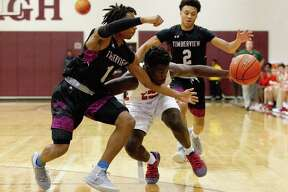 The Woodlands guard Ja?'Korey Randle (10) drives against Mansfield-Timberview guards CJ Smith (1) and-Timberview guard Marquiss Childs (2) in the first quarter of a game during the Doghouse Invitational at Magnolia High School, Saturday, Nov. 17, 2018, in Magnolia.