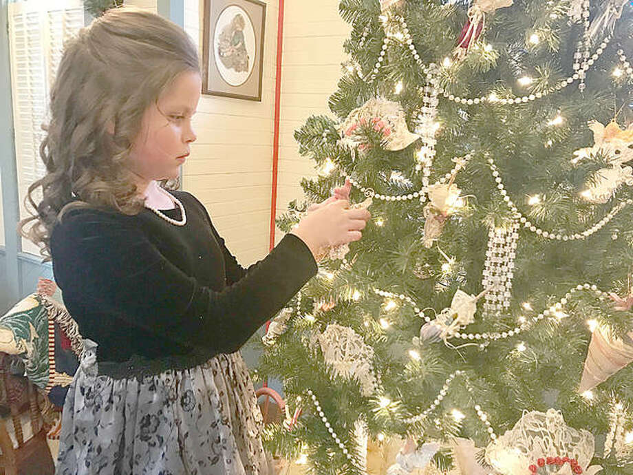 Grace Harner, 9, hangs an ornament on the tree inside the Lucy Haskell Playhouse. Harner will be playing the part of Lucy Haskell at the playhouse Christmas party on Dec. 1. Photo: Riley Newton | The Telegraph