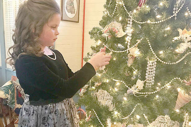 Grace Harner, 9, hangs an ornament on the tree inside the Lucy Haskell Playhouse. Harner will be playing the part of Lucy Haskell at the playhouse Christmas party on Dec. 1.