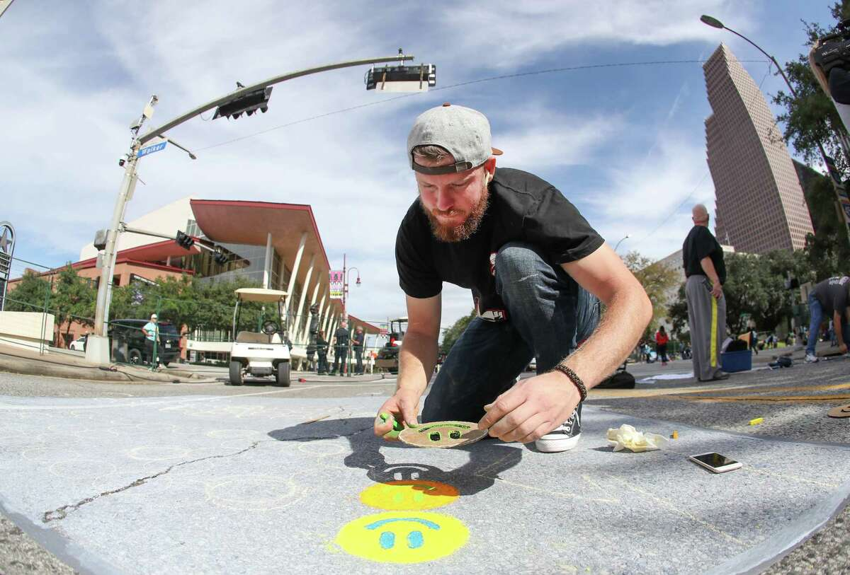 Houston Astros Pitcher Chris Devenski places smiley faces on his street mural during Houston Via Colori Saturday, Nov. 17, 2018, in Houston. The streets of downtown transformed into a colorful artspace by more than 200 artists at the annual Via Colori festival. The two day event benefits the Center for Hearing and Speech. The event goes through Sunday afternoon.