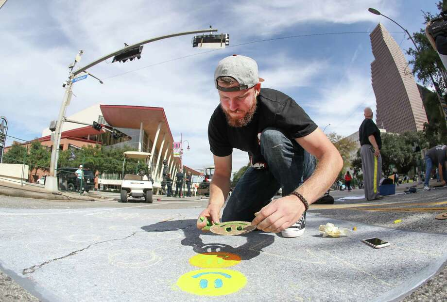 Houston Astros Pitcher Chris Devenski places smiley faces on his street mural during Houston Via Colori Saturday, Nov. 17, 2018, in Houston. The streets of downtown transformed into a colorful artspace by more than 200 artists at the annual Via Colori festival. The two day event benefits the Center for Hearing and Speech. The event goes through Sunday afternoon. Photo: Steve Gonzales, Staff Photographer / © 2018 Houston Chronicle