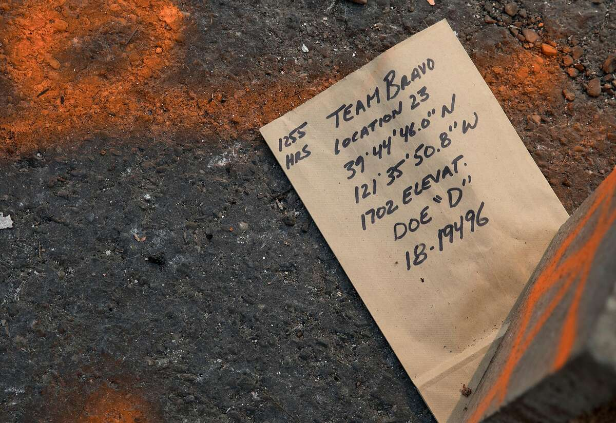 A note marking the discovery of human remains sits in the driveway of a charred home in Holly Hills Mobile Estates in Paradise, Calif. Saturday, Nov. 17, 2018 after the Camp Fire ripped through the town, destroying most structures.