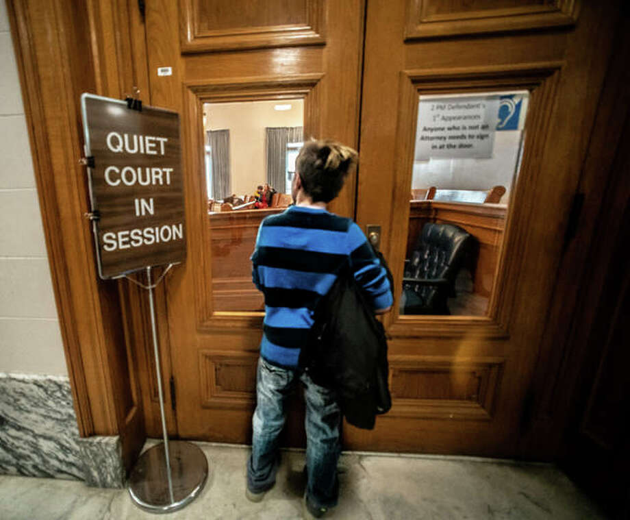 A young boy peers into a courtroom Saturday at the Madison County Courthouse during the judiciary's annual Adoption Day proceedings, where nearly 50 children officially became part of a family. Madison County's Adoption Day celebration has grown to be one of the largest in the United States in the last two years. Photo: Nathan Woodside | Hearst Newspapers