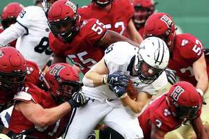 Yale's Zane Dudek is tackled during Saturday's game against Harvard at Fenway Park in Boston.