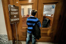 A young boy peers into a courtroom Saturday at the Madison County Courthouse during the judiciary's annual Adoption Day proceedings, where nearly 50 children officially became part of a family. Madison County's Adoption Day celebration has grown to be one of the largest in the United States in the last two years.