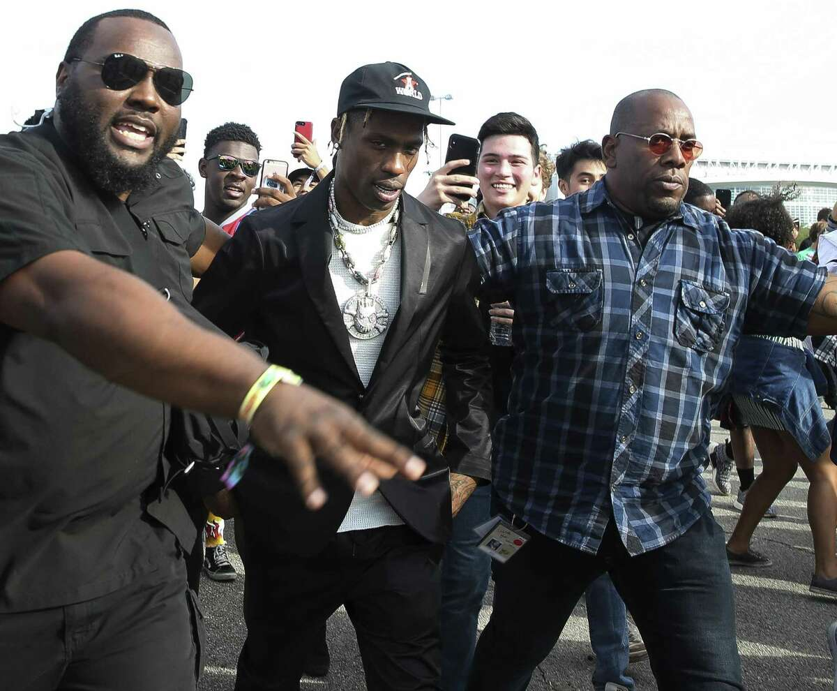 Rapper Travis Scott is swarmed by fans while briefly entering the Astroworld Festival grounds at NRG Park on Saturday, Nov. 17, 2018, in Houston. Bodyguards helped Scott exit the fairground quickly.