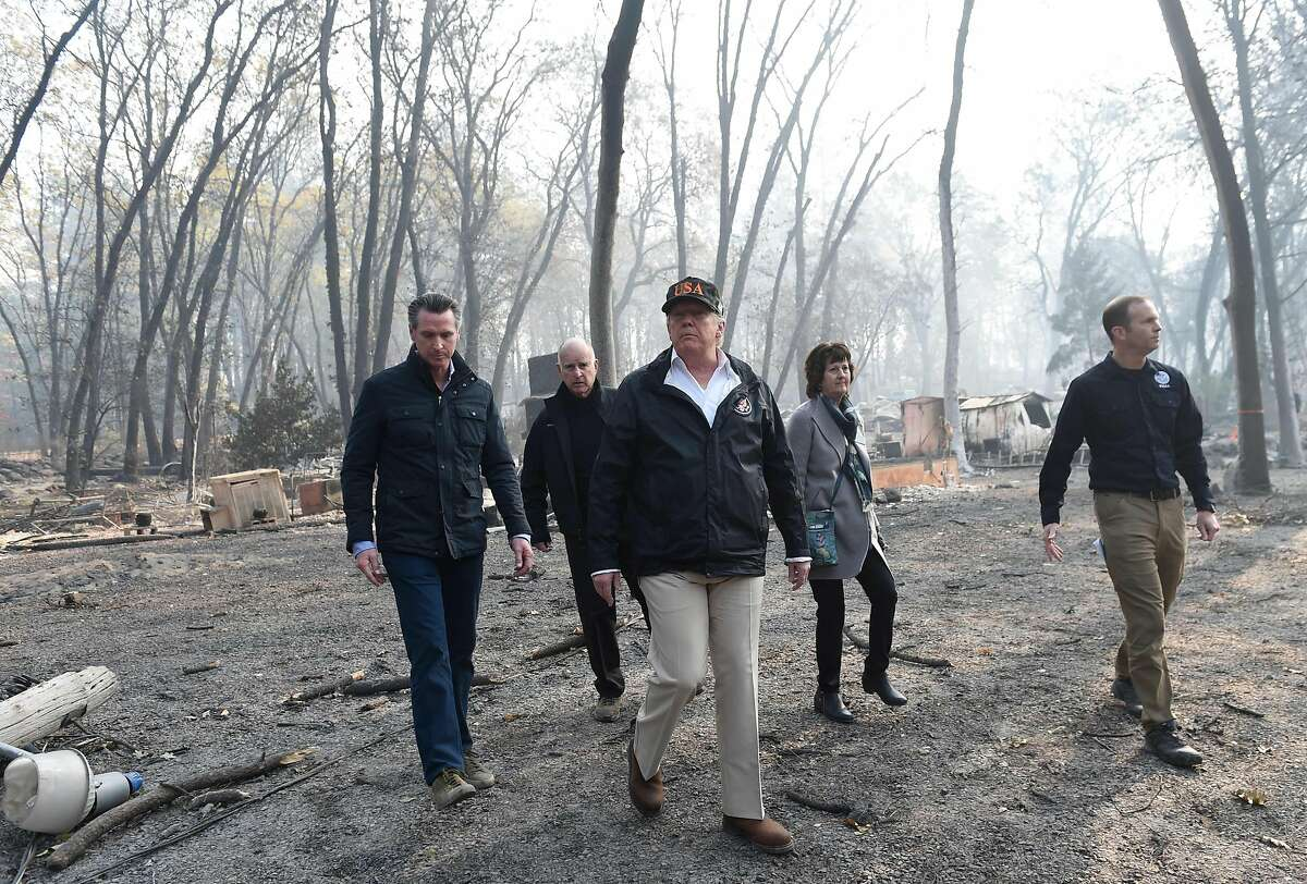 """US President Donald Trump (C) walks with Paradise Mayor Jody Jones (2R), Governor of California Jerry Brown (2L), Administrator of the Federal Emergency Management Agency, Brock Long (R), and Lieutenant Governor of California, Gavin Newson, as they view damage from wildfires in Paradise, California on November 17, 2018. - President Donald Trump arrived in California to meet with officials, victims and the """"unbelievably brave"""" firefighters there, as more than 1,000 people remain listed as missing in the worst-ever wildfire to hit the US state. (Photo by SAUL LOEB / AFP)SAUL LOEB/AFP/Getty Images"""