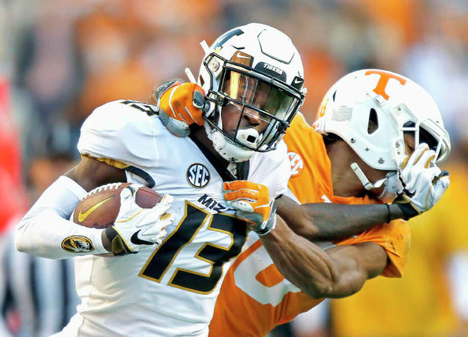 Missouri wide receiver Kam Scott (13) tries to escape the grasp of Tennessee defensive back Nigel Warrior (18) Saturday, in Knoxville, Tenn. Photo: Wade Payne | AP Photo
