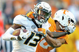 Missouri wide receiver Kam Scott (13) tries to escape the grasp of Tennessee defensive back Nigel Warrior (18) Saturday, in Knoxville, Tenn.