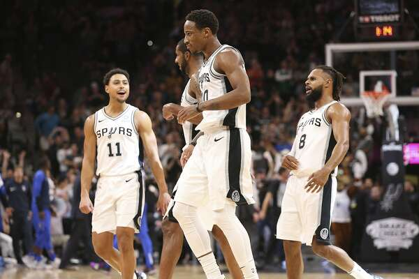 The San Antonio Spurs, including San Antonio Spurs' Bryn Forbes, left, and Patty Mills react after DeMar DeRozan hits a last second three-pointer in overtime against the Dallas Mavericks at the AT&T Center, Monday, Oct. 29, 2018.