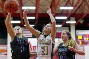 Willis guard Mya Villarreal (1) looks to grab a rebound against Montgomery point guard Lindsey Hefner (21) and guard Ali McNew (13) in the third quarter of a game duing the Splendora baketball tournament, Saturday, Nov. 17, 2018, in Splendora.