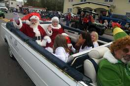 Santa and Mrs. Claus, left, along with Elf Wesley Burke, right, bring up the end of the rear of the Tomball Christmas Parade on Main Street in downtown Tomball on Nov. 17, 2018.