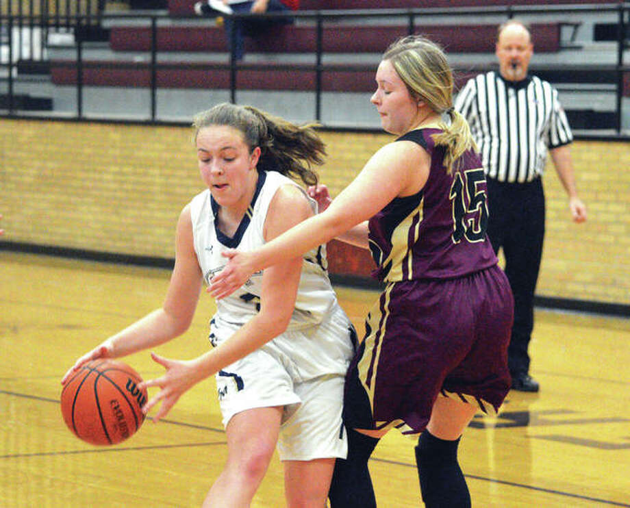 Father McGivney freshman Charlize Luehmann, left, drive to the basket on Saturday against East Alton-Wood River during the championship game of the Dupo Cat Classic. Photo: Scott Marion/Intelligencer