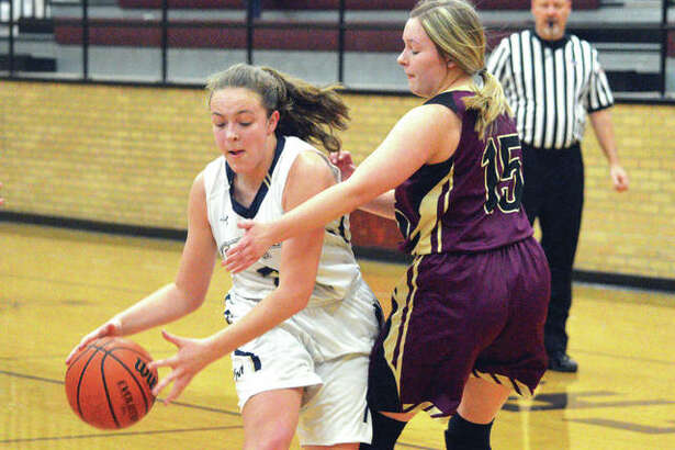 Father McGivney freshman Charlize Luehmann, left, drive to the basket on Saturday against East Alton-Wood River during the championship game of the Dupo Cat Classic.