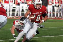 Sacred Heart QB Kevin Duke evades Saint Francis' Jake Curry during Saturday's game in Fairfield.