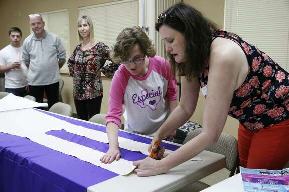 Sandy Liwang, right, demonstrates how to cut a pattern with help from Emma Barron, 20, at a cape-making workshop at Abiding Presence Lutheran Church.